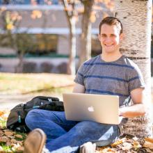 student sitting against tree, with his laptop